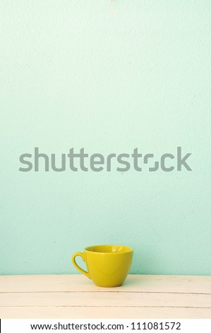 Green coffee cup on the white wood with green grunge wall background - stock photo