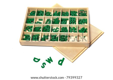 Green colored movable alphabets for kids learning on white background with container - stock photo