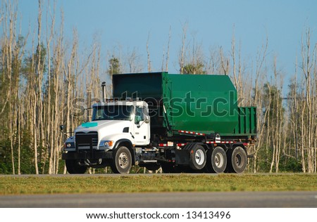 Green colored waste removal dump truck - stock photo