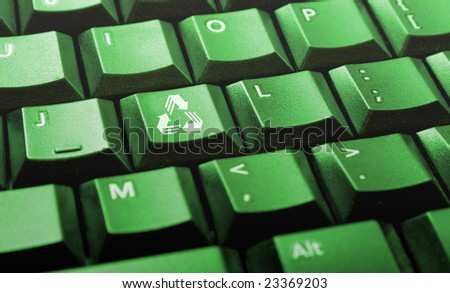 Green computer keyboard with recycle logo on one of the keys