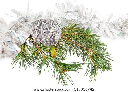 Green conifer branch with silver ball and tinsel isolated on white - stock photo