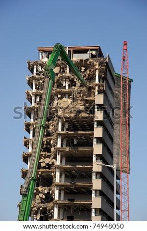 Green crane demolishing a highrise building - stock photo