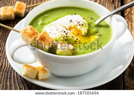 Green cream soup with poached egg and croutons