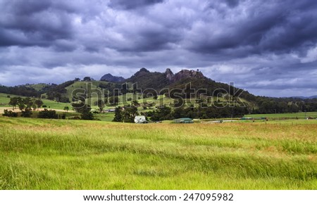 green cultivated agricultural field against distant rocky mountain under stormy cloud sky in picturesque country of regional NSW Australia - stock photo