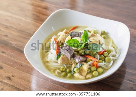 Green curry chicken with Thai rice noodles in white plate on wood table. Thai Food.
