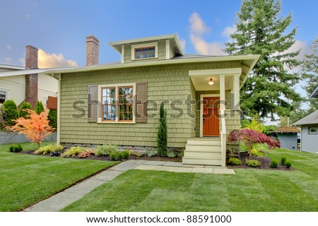 Green cute small craftsman house with orange door - stock photo