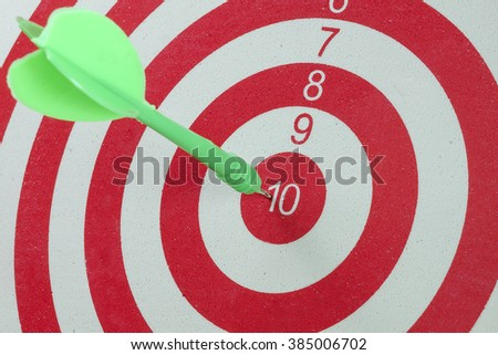 Green dart arrow hitting in the target center of dartboard - stock photo