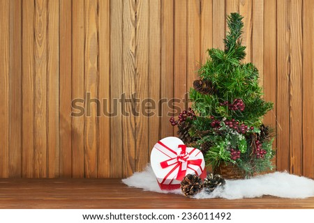 Green Decorated Christmas Tree and Gift on Wooden Background. Closeup. - stock photo