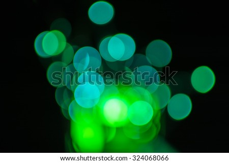 Green defocused bokeh Christmas lights on a wooden support - stock photo