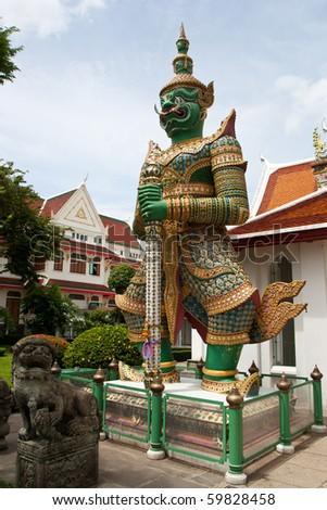 Green demon stands to watch temple door - stock photo