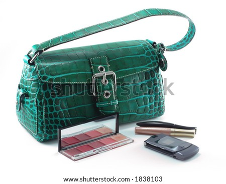 Green designer bag with mobile phone and cosmetics - stock photo