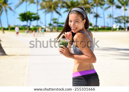 Green detox cleanse vegetable smoothie woman. Healthy sport woman runner drinking fresh and happy after running. Fitness and healthy lifestyle concept with multicultural Asian Caucasian female model. - stock photo