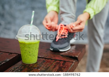 Green detox smoothie cup and woman lacing running shoes before workout on rainy day. Fitness and healthy lifestyle concept. - stock photo
