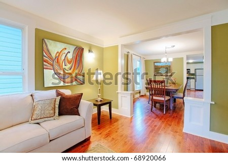 Green dining and living room with nice furniture and art. - stock photo