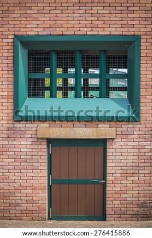 Green door color as brick wall - stock photo