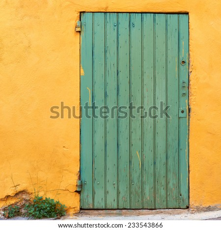 Green door on yellow wall in French village, typical colors of Provence - stock photo