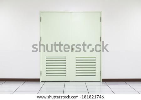 Green door with white wall background. - stock photo