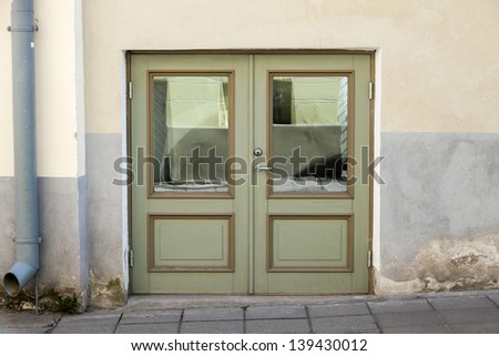 Green double door with decoration elements in old building facade. Tallinn, Estonia - stock photo