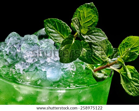 Green drink  with crushed ice on dark background. Top view. - stock photo