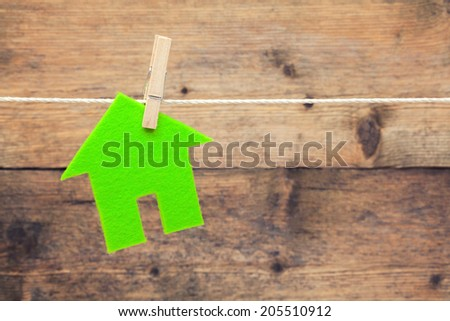 Green eco house attach to rope with clothes pins on wooden background - stock photo