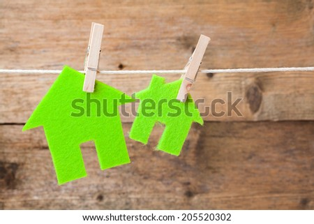 Green eco houses attach to rope with clothes pins on wooden background - stock photo