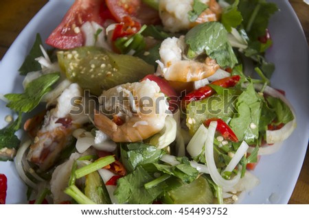 Green Eggplant Spicy Salad with meat and seafood thai style for sale at restaurant - stock photo