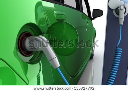 Green electric car at charging station with power outlet - stock photo
