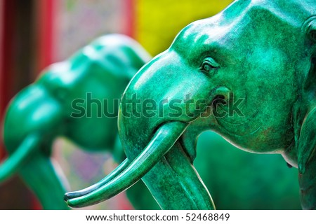 Green elephant statue in front of temple gates. - stock photo
