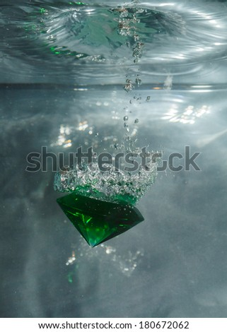 Green emerald falling through the water against a grey background - stock photo