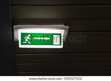 Green emergency exit sign on white at a airport  - stock photo