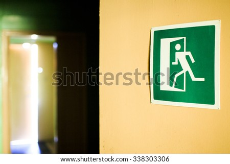 green emergency exit sign showing the open door in the distance. emergency exit sign on the wall indicating the way to the evacuation of the building. in the distance the light from the open door - stock photo