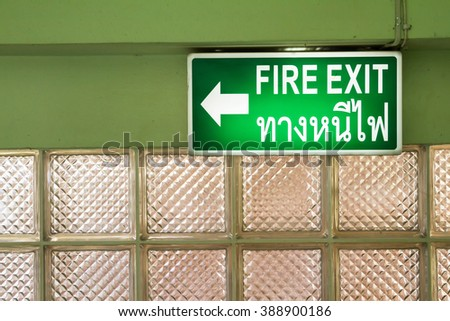 """Green emergency fire exit sign showing the way to escape.""""Thng nee fi"""" is Fire exit in Thai Language. - stock photo"""