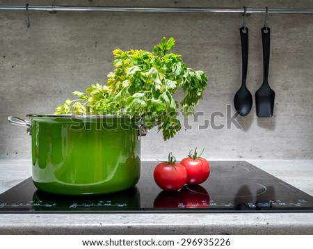 Green enamel stewpot with parsley and two tomatoes on black induction cooker - stock photo