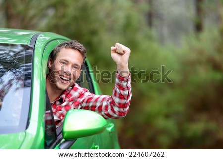 Green energy biofuel electric car driver happy and excited. Man driving new vehicle in cheerful in nature forest. Young male driver looking at camera with arm raised cheering. - stock photo