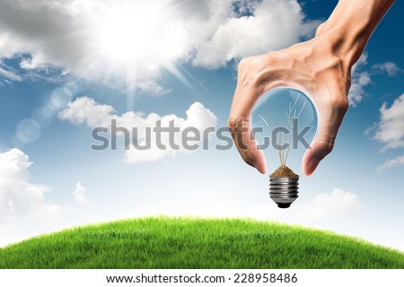 Green energy concept - dry tree branch in bulb and grass field with bulb shaped hand on blue sky and cloud background - stock photo