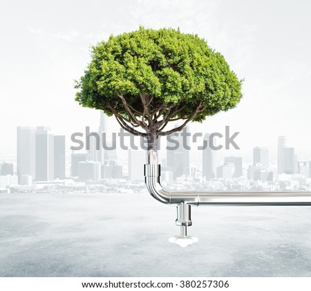 Green energy concept with tree and water tap at city background - stock photo