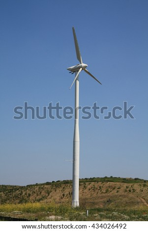 Green energy generating wind turbine in a blue sky - stock photo