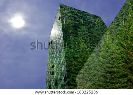 Green energy in the city: modern building covered with spruce forest - stock photo