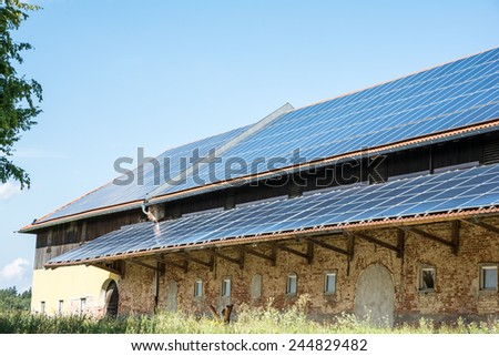 Green energy with solar panels on a old agricultural building - stock photo