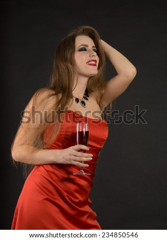 Green-eyed girl in a  red dress drink a wine. - stock photo