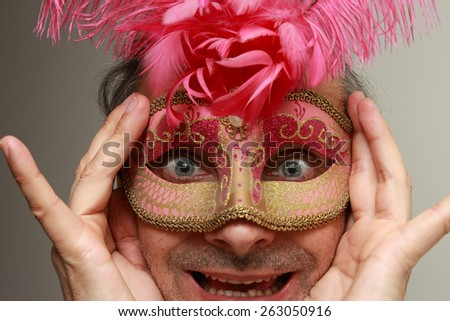 green eyed man at the masquerade with feminine mask - stock photo