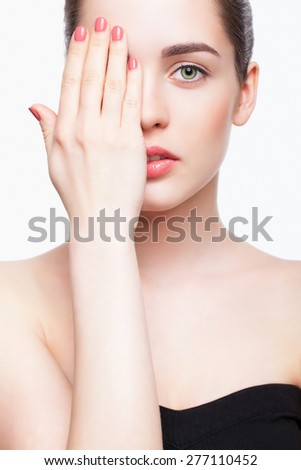 Green-eyed young beautiful woman in black dress closing eye by hand - stock photo
