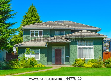 Green family house on a sunny day in Vancouver, Canada. - stock photo