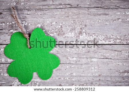 Green felt shamrock cutout on a vintage wooden distressed table for St. Patrick's Day - stock photo