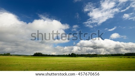 Green field against blue sky and clouds - stock photo