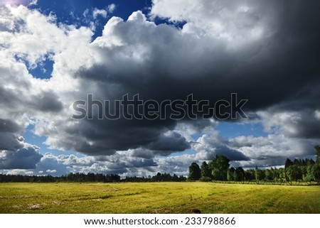 Green field against rainy clouds - stock photo