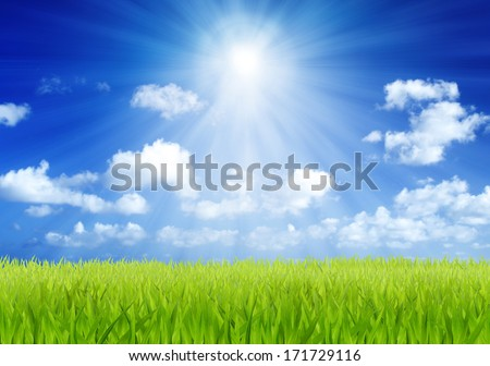 Green field and blue sky with sun beam background - stock photo