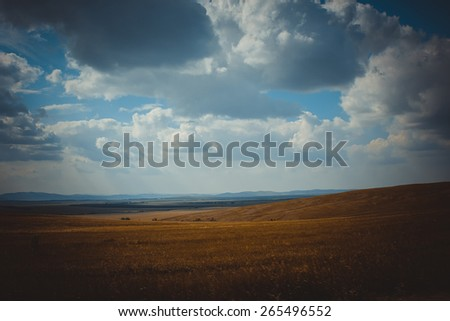 Green field and bright blue perfect sky with clouds. The mountains landscape, The hills in the fog. Morning and day green landscape, horizons. Summer background. Fantastic place  - stock photo