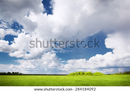 green field and dramatic sky - stock photo