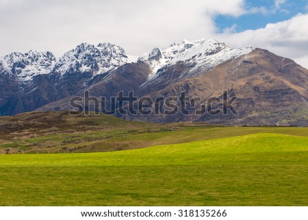 green field and mountain landscape with blue sky - stock photo